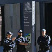 Police stand guard outside Parramatta Court, where two men charged with terrorism offenses with a plan to blow up a passenger plane, appeared via video link in Sydney on Friday. A senior Islamic State commander directed a group of Australian men to build a bomb destined for an Etihad Airways flight out of Sydney, with a second poisonous gas plot also in the works, police alleged Friday. | AFP-JIJI