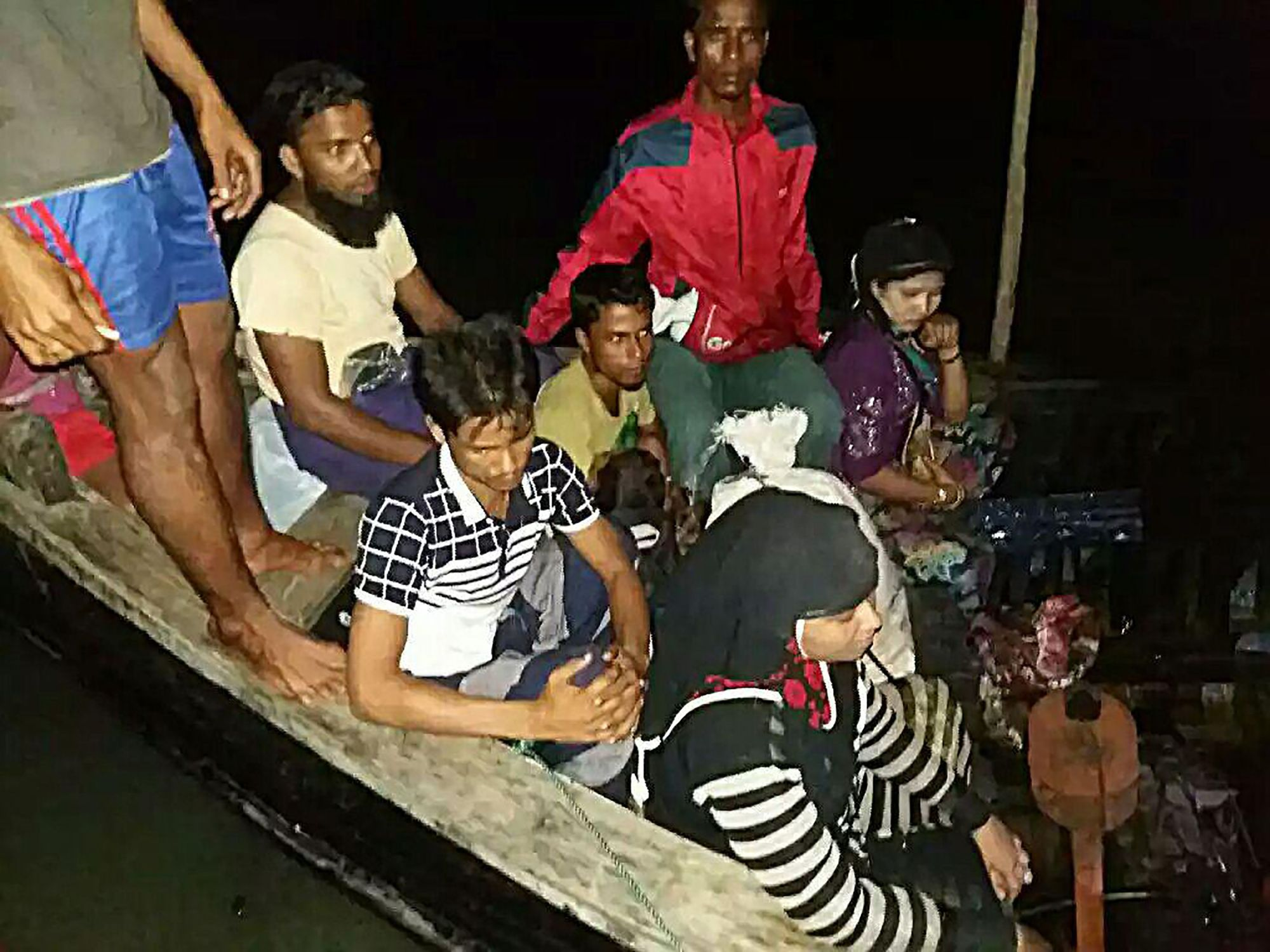 Rohingya refugees fleeing from Myanmar sit in a boat after the Bangladesh coast guard stopped them Saturday on the Naf river from entering the country. The coast guard pushed back a boat full of 31 Rohingya Muslims on a bordering river as they were escaping a fresh army buildup in neighboring Myanmar, an official said.   BANGLADESH COAST GUARD HANDOUT / VIA AFP-JIJI