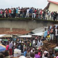 Mourners look on as victims of a mudslide are buried at the cemetery of Freetown on Thursday.   AFP-JIJI