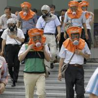 South Koreans wearing gas masks flee a mock attack as part of the Ulchi Freedom Guardian exercises in Seoul in August 2010. | AP