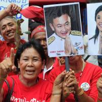 Thai Red Shirts, backers of fugitive former leader Thaksin Shinawatra — pictured with his sister, former Prime Minister Yingluck Shinawatra on a placard — shout slogans as they gather in support of the two in Bangkok in August 2011. | AFP-JIJI