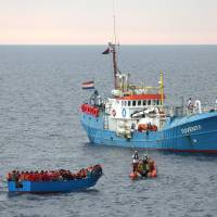 Migrants on a wooden boat are rescued by the German NGO Jugend Rettet ship Juventa crew in the Mediterranean off Libya's coast June 18.   REUTERS