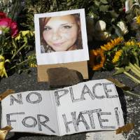 A makeshift memorial of flowers and a photo of victim Heather Heyer are seen in Charlottesville, Virginia, Sunday. Heyer died when a car rammed into a group of people who were protesting the presence of white supremacists who had gathered in the city for a rally. | AP