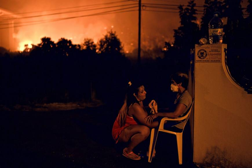 A woman tries to calm her neighbor as wildfire approaches the village following a new rash of forest fires ahead of a weekend of warm temperatures, at Rio de Moinhos village in Abrantes, Portugal, Sunday. Some 1,800 firefighters backed by hundreds of vehicles were trying to douse around 10 fires across the country, authorities said. | AFP-JIJI
