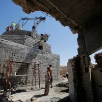 Workers rebuild a Yazidi shrine, after is was destroyed by Islamic State, in Bashiqa, a town near Mosul, Iraq, Tuesday. | REUTERS
