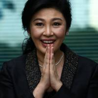 Ousted former Thai Prime Minister Yingluck Shinawatra greets supporters as she arrives at the Supreme Court in Bangkok on Aug. 1. | REUTERS