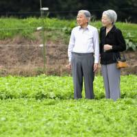 Emperor Akihito and Empress Michiko walk in a cabbage patch in the town of Karuizawa, Nagano Prefecture, last week. POOL / VIA KYODO