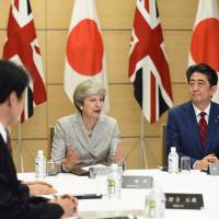 British Prime Minister Theresa May speaks while Prime Minister Shinzo Abe looks on during a meeting of Japan's National Security Council at Abe's official residence in Tokyo on Thursday. | REUTERS