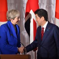British Prime Minister Theresa May shakes hands with her Japanese counterpart, Shinzo Abe, following their joint news conference Thursday at the State Guesthouse in Tokyo's Akasaka district. | POOL / VIA REUTERS