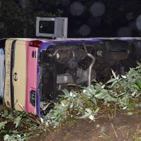 A tourist bus is shown on its side Friday after veering off National Route 274 and tipping over in Shimizu, Hokkaido, earlier in the day. | KYODO