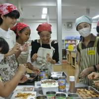 Participants at the Kita Kuma children's diner in Tokyo's Kita Ward prepare desserts on July 21. | KYODO