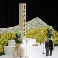 Emperor Akihito and Empress Michiko bow before an altar decorated with a bank of chrysanthemums during a memorial service at Nippon Budokan hall in Tokyo on Tuesday as Japan marked the 72nd anniversary of its World War II surrender. | AP