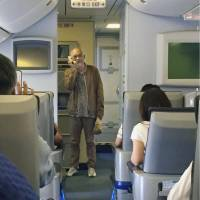 Folk singer Chiharu Matsuyama sings his hit song on a plane Sunday at a Hokkaido airport, in this photo taken by a passenger. | KYODO