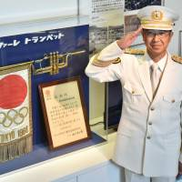 Kazuyuki Yoneda, head of Aichi Prefectural Police band, poses next to a trumpet that was used during the 1964 Tokyo Olympics. | CHUNICHI SHIMBUN