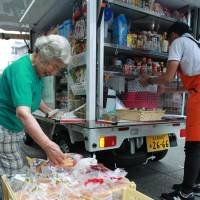 An elderly woman checks items in a mobile supermarket in front of her home in Minato Ward, Nagoya. | CHUNICHI SHIMBUN