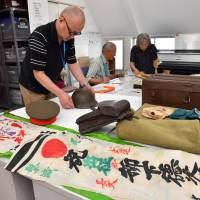 Volunteers sort out personal items donated by relatives of people who experienced World War II at the Material Pavilion of War and Peace Aichi in Nagoya. | CHUNICHI SHIMBUN
