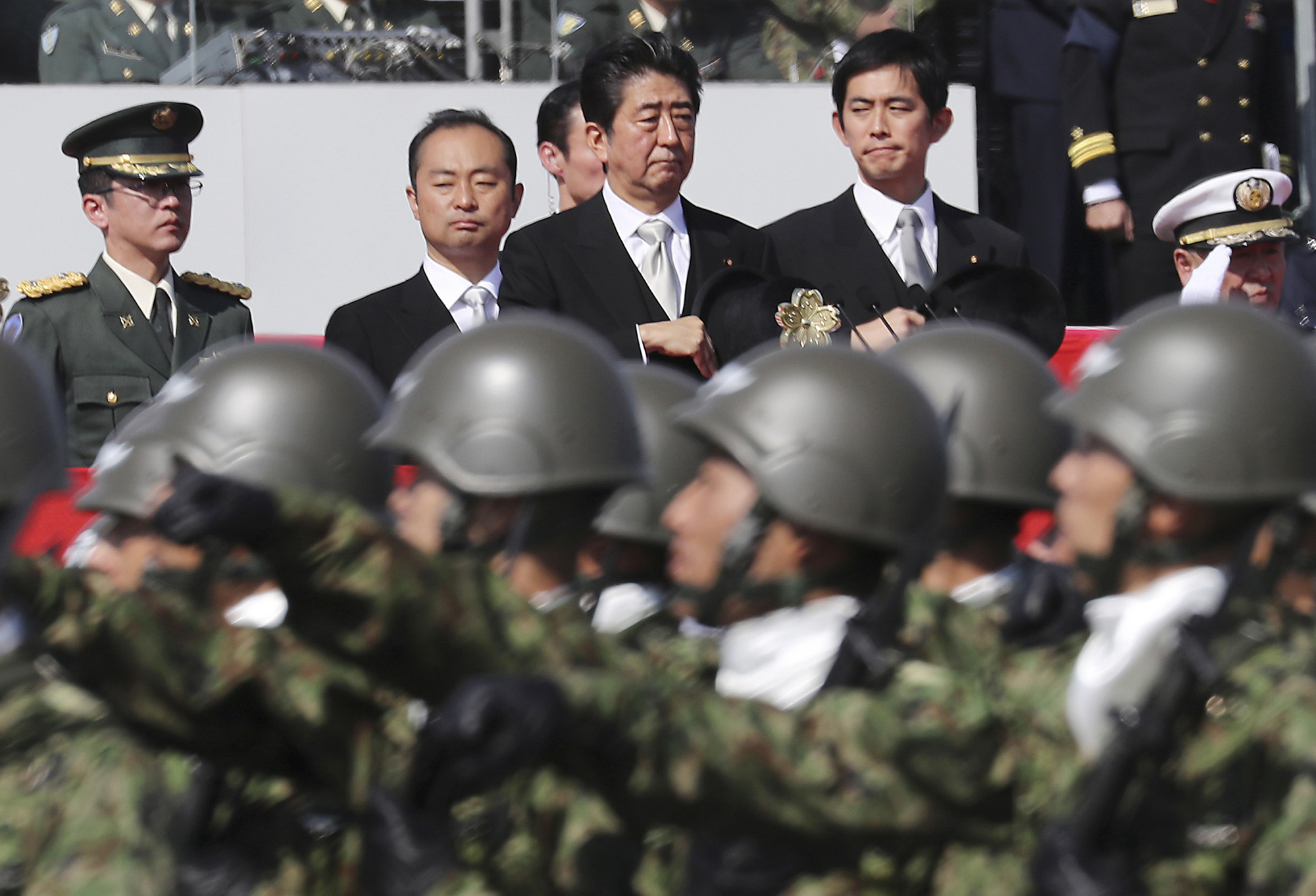 Prime Minister Shinzo Abe reviews members of the Self-Defense Forces during a parade at a military base in Asaka, Saitama Prefecture, in October. | AP