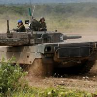 Japan Ground Self Defense Force members riding a Type 90 tank take part in a joint exercise with U.S. Marine Corps personnel in Eniwa, Hokkaido, on August 16. | REUTERS