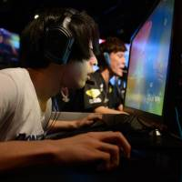 Participants compete in an e-Sports event in Tokyo on July 1. Laws curbing organized crime and gambling are preventing gaming competitions with high prize money from being held in Japan. | BLOOMBERG