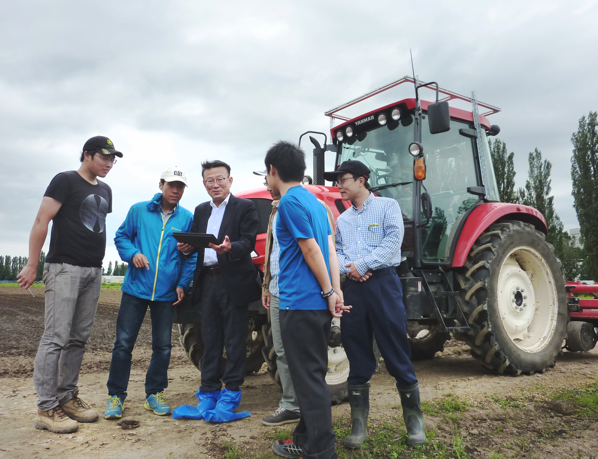 Hokkaido University professor Noboru Noguchi (center) oversees a test on a tractor operated with a tablet computer on the university campus in Sapporo on June 27. | KYODO