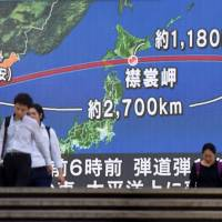 Pedestrians walk in front of a huge screen displaying a map of Japan and the Korean Peninsula, in Tokyo on August 29. | AFP-JIJI