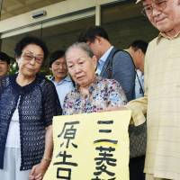 Kim Jae-rim (center), one of the South Koreans suing Mitsubishi Heavy Industries, holds up a sign announcing victory on Friday after the Gwangju District Court ordered the heavy machinery maker to pay Kim and three other victims of forced labor during the war 470 million won in compensation. | KYODO