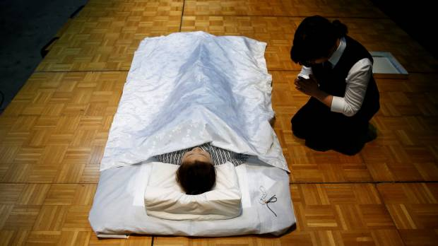 A funeral undertaker prays next to a model during an ceremonial nōkan (encoffining) competition at Life Ending Industry EXPO 2017 in Tokyo on Thursday.
