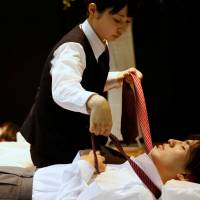 A funeral undertaker dresses a model during an encoffinment competition at Life Ending Industry EXPO 2017 in Tokyo.   REUTERS