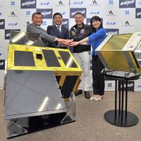 Toyoyuki Nagamine (right), a vice president at ANA Holdings Inc., Nobu Okada (center right), CEO of Astroscale PTE Ltd., Jiro Osawa (center left), an OSG Corp. executive, and astronaut Naoko Yamazaki join hands at a news conference in Tokyo on July 14 to show off a life-sized model of the debris-removal satellite ELSA-d, which is under development. | YOSHIAKI MIURA