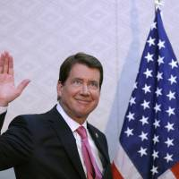 New U.S. Ambassador to Japan William Hagerty waves during a news conference on his arrival at Narita International Airport on Thursday. | AP