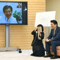 Prime Minister Shinzo Abe tries out a telemedicine system offered by Minamisoma, Fukushima Prefecture, in May at the Prime Minister's Office. | KYODO