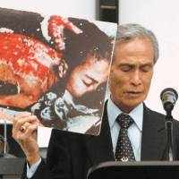 A-bomb survivor Sumiteru Taniguchi, who died Wednesday at the age of 88, gives a speech in May 2010 at the U.N. conference in New York on reviewing the Nuclear Non-Proliferation Treaty, with a picture of himself suffering from severe burns caused by the U.S. atomic bombing of Nagasaki in 1945. | KYODO