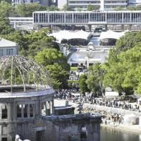The Atomic Bomb Dome looms in the foreground as people gather at Hiroshima's Peace Memorial Park on Sunday to mark the 72nd anniversary of the U.S. nuclear attack on the city on Aug. 6, 1945. | KYODO