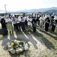 Residents offer prayers on the third anniversary of the deadly landslides that killed 77 people in  Hiroshima at the site of a house that once stood in the city's Asaminami Ward. | KYODO