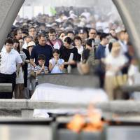 People offer prayers in front of the cenotaph dedicated to atomic bomb victims at Peace Memorial Park in Hiroshima on Sunday. | KYODO
