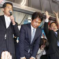 Kazuhiko Oigawa (center), a former trade ministry bureaucrat, bows to supporters after media outlets of Sunday predicted him the winner of the Ibaraki gubernatorial election. | KYODO
