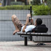A man looks at his smartphone while lying on a bench outside JR Kichijoji Station in Musashino, Tokyo, on Wednesday. | BLOOMBERG