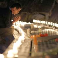 A man on Saturday prays for those killed in the 1985 crash of JAL Flight 123 in the village of Ueno, Gunma Prefecture, before a stone engraved with the victims' names. | KYODO