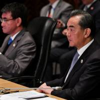 Chinese Foreign Minister Wang Yi (right) and Foreign Minister Taro Kono listen to Philippine Foreign Secretary Alan Peter Cayetano's opening remarks during the 18th ASEAN Plus Three Foreign Ministers Meeting in Manila on Monday. | POOL / VIA REUTERS