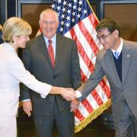 Foreign Minister Taro Kono shakes hands with Australian Foreign Minister Julie Bishop as U.S. Secretary of State Rex Tillerson looks on during a meeting in Manila on Monday.   KYODO