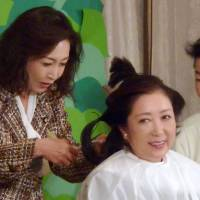 Yuriko Koike, then a Liberal Democratic Party lawmaker, has her hair trimmed by fellow Diet member Junko Mihara in December 2012. Koike had vowed not to cut her hair until the LDP returned to power. | KYODO