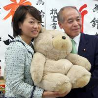 House of Representatives lawmaker Takako Suzuki poses with her father, Muneo, a former Lower House lawmaker, in Kushiro, Hokkaido, in this file photo from December 2014. | KYODO