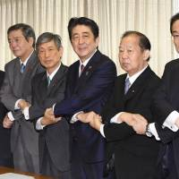 Prime Minister Shinzo Abe joins hands with the ruling Liberal Democratic Party's new leadership, including newly appointed LDP policy chief Fumio Kishida (right) at the party headquarters in Tokyo on Thursday. | KYODO