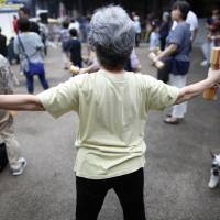 A woman exercises in Tokyo in September 2016. Kyoto Prefectural University of Medicine and Hirosaki University will launch a survey in the Tango district in northern Kyoto Prefecture to study the longevity of residents there. | BLOOMBERG