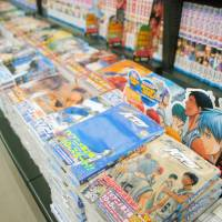 Piles of comic books on the shelves are the norm in most bookstores in Japan. But this could change with the rise of digital comics. | KYODO