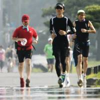 Runners brave heat as they jog around the Imperial Palace in central Tokyo. | KYODO