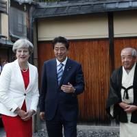 British Prime Minister Theresa May is welcomed by Prime Minister Shinzo Abe and tea master Sen Sosa upon her arrival for a tea ceremony at the Omotesenke school's Fushinan teahouse in Kyoto on Wednesday. | POOL / VIA AP