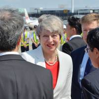 Japanese officials greet arriving British Prime Minister Theresa May at Itami Airport in Osaka Wednesday. | AFP-JIJI