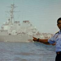 A Malaysia Maritime Enforcement Agency officer points to a hole in the USS John S. McCain during a news conference in Putrajaya, Malaysia, on Monday. | REUTERS