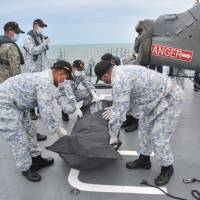 Royal Malaysian Navy personnel carry a body onto their ship during a search and rescue operation for survivors of the USS John S. McCain ship collision in this undated photo released Tuesday. | REUTERS